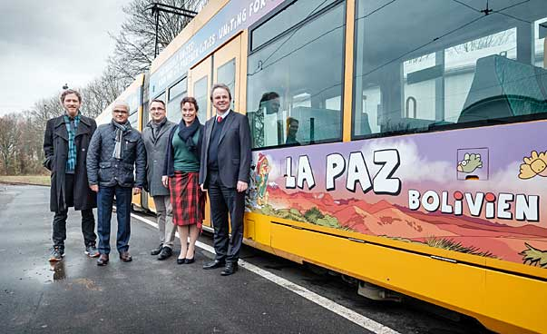 Five people stand to the left of a colorfully illustrated tram.