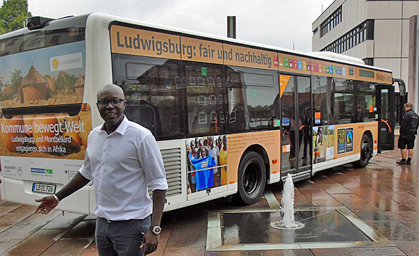 A man is standing in front of a bus, which is printed with different pictures and texts.