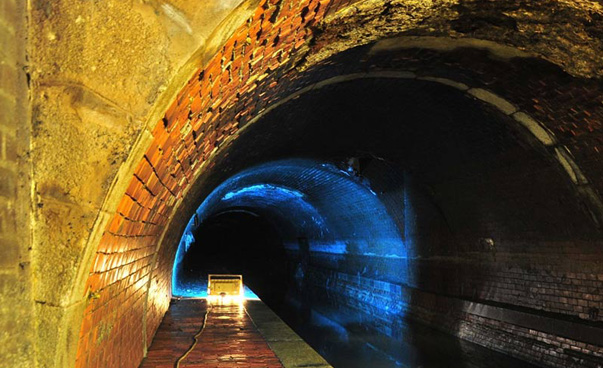 A colorfully illuminated sewer tunnel