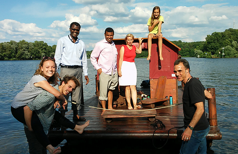 A group of people is standing on a boat floating on a lake.