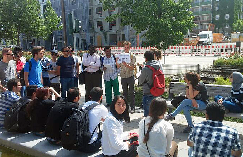 A group of young people is listening to a young man with a map in his hands.