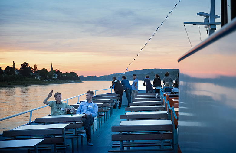Rhine navigation at sunset with a view of the Siebengebirge. In the background several participants stand at the railing and observe the landscape.