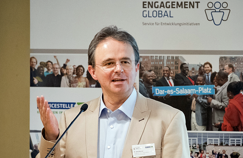Dr. Jens Kreuter, Managing Director of Engagement Global, welcoming the participants to the Second Regional Conference on Asia. He stands behind a lectern with a microphone and gestures with his right hand. In the background is a banner from Engagement Global.