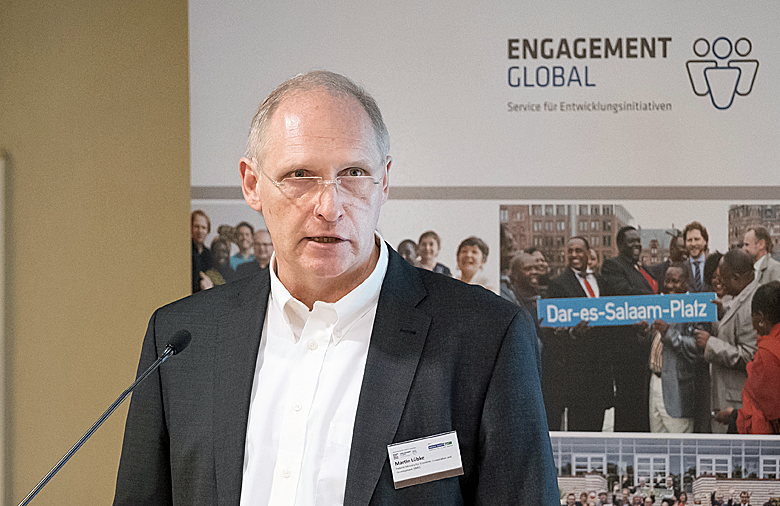 Martin Lübke from the BMZ stands behind the lectern to which a microphone is attached. On the desk are his name tag and a glass of water. In the background is a banner from Engagement Global.