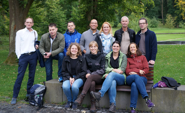 The participants of the team workshop in Königswinter pose outside, in the background there are trees for the camera.