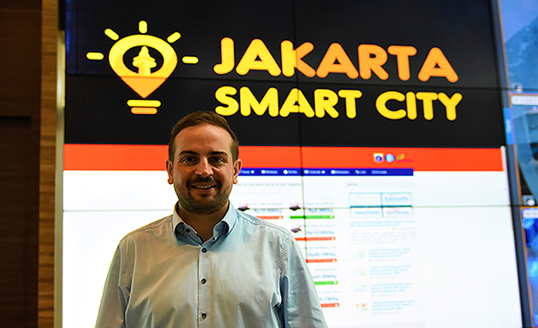 "Kariem El-Ali stands in front of a sign with the inscription ""Jakarta Smart City"""
