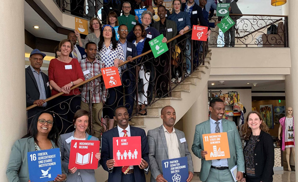 Approximately 30 people can be seen. Some of them are standing on a staircase, holding up banners with the symbols of the global sustainability goals.
