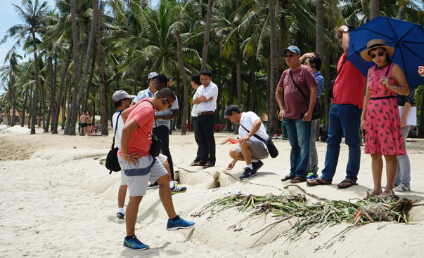 Participants at a beach looking at sandbags as part of coastal protection.