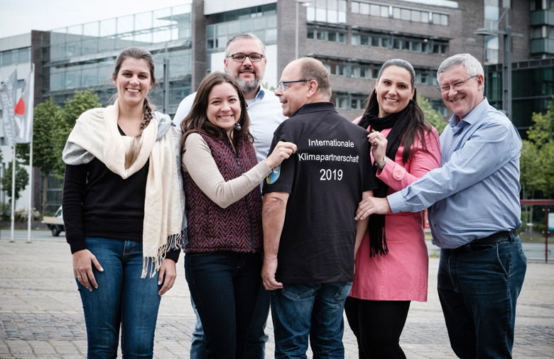 Six laughing people can be seen; in the background a modern building. A man stands with his back to the observer. At the back of his shirt is written: International Climate Partnership 2019.