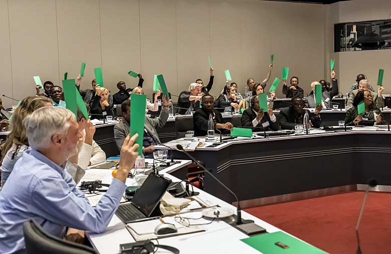 An audience is holding green coloured cards.
