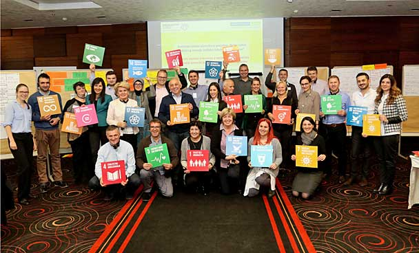 This group photo shows participants at the network meeting of 'Municipal Partnerships for Sustainability' in Sarajevo. Participants are standing in the conference room in front of partitions, holding up boards showing the 17 SDGs.