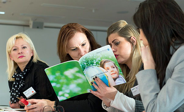 Participants of the workshop reading in a brochure.