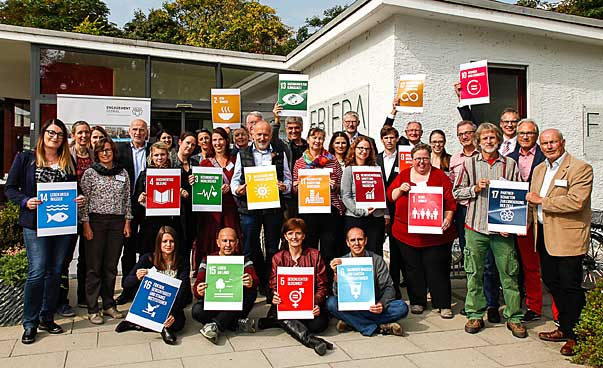 A group smiles at the camera, some of the people carry signs with the symbols of the 17 sustainable development targets.