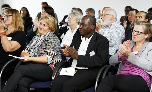 Conference participants applauding.